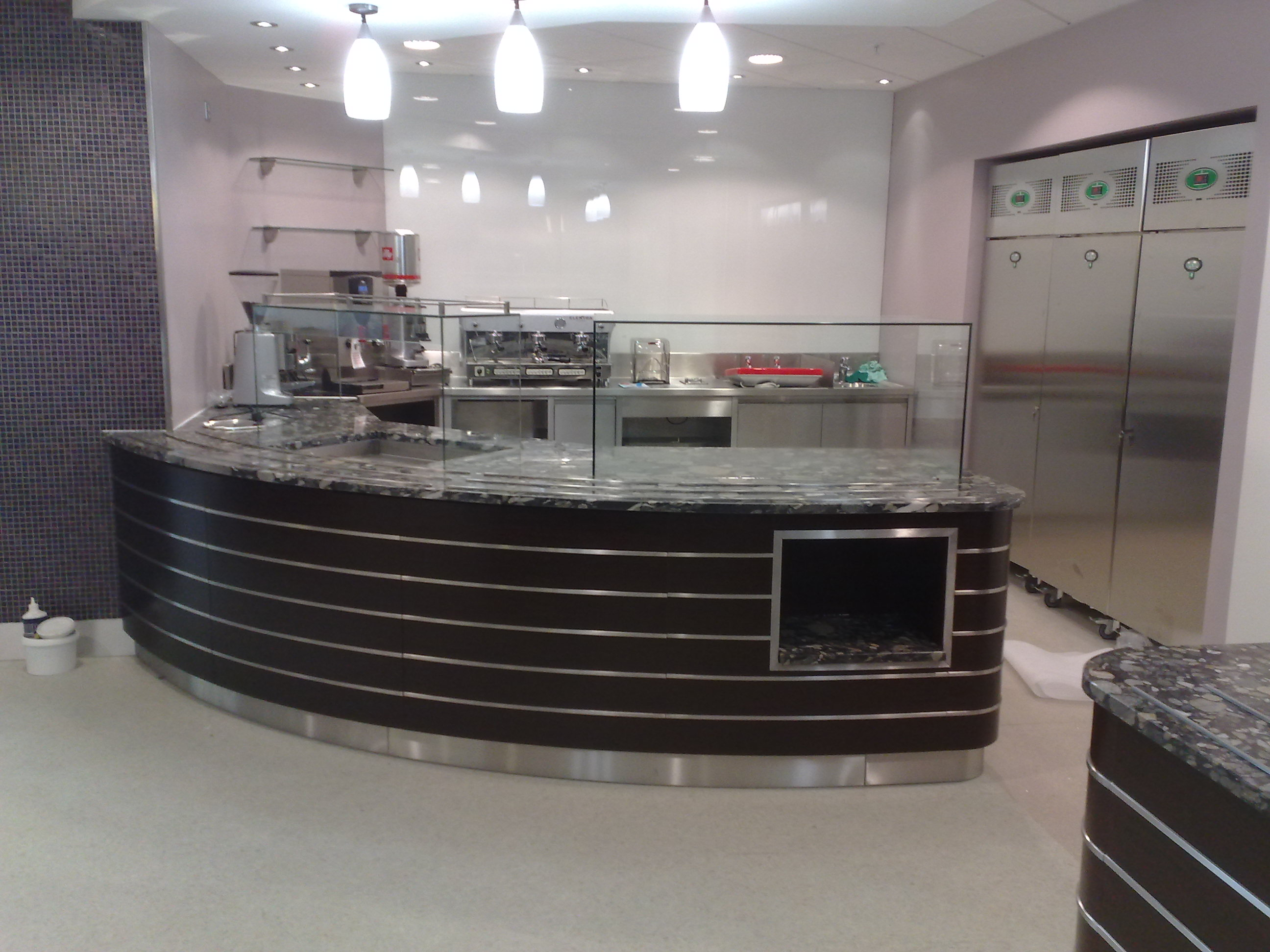 Department store –London.  Food servery – tops are granite . Fascia panels in wenge Laminate with inset stainless steel  bar
