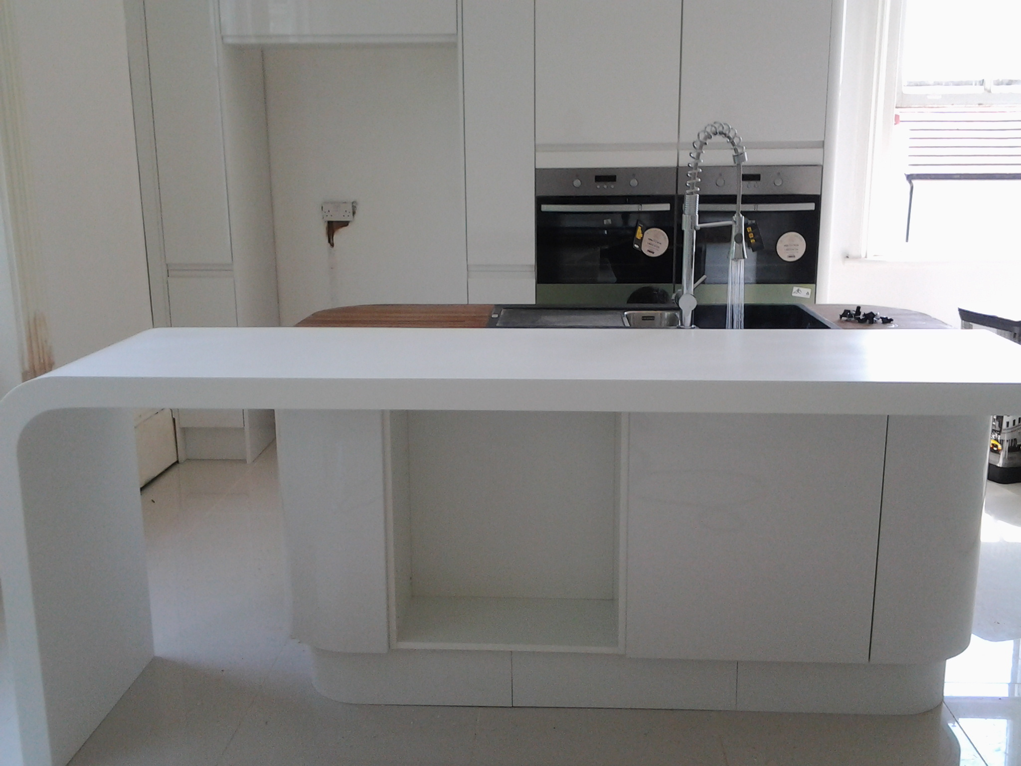 Glacier white corian worktop with formed curved end panels