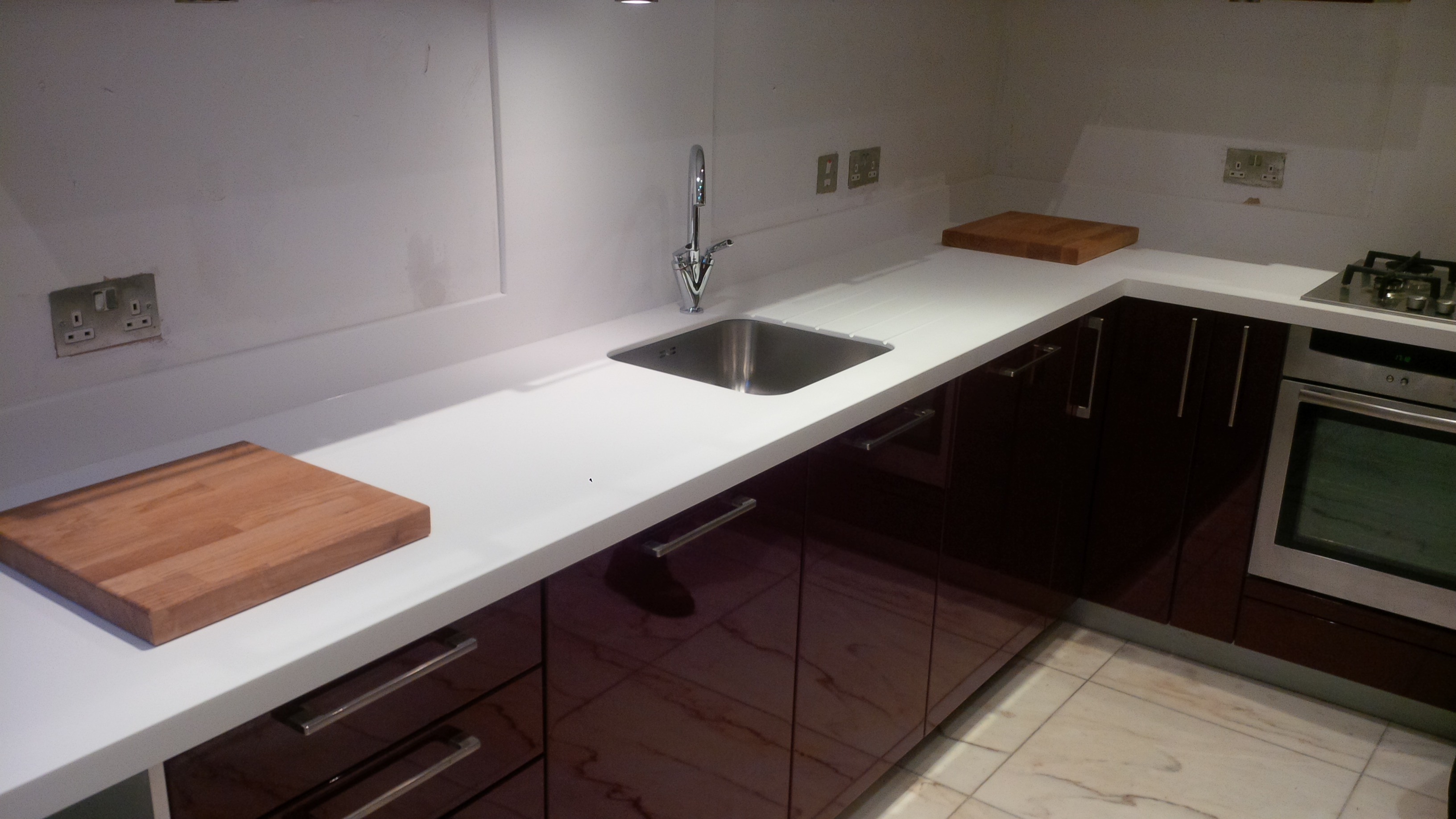 Replacement of granite worktops and upstands to glacier white corian and fitting of stainless steel  sink