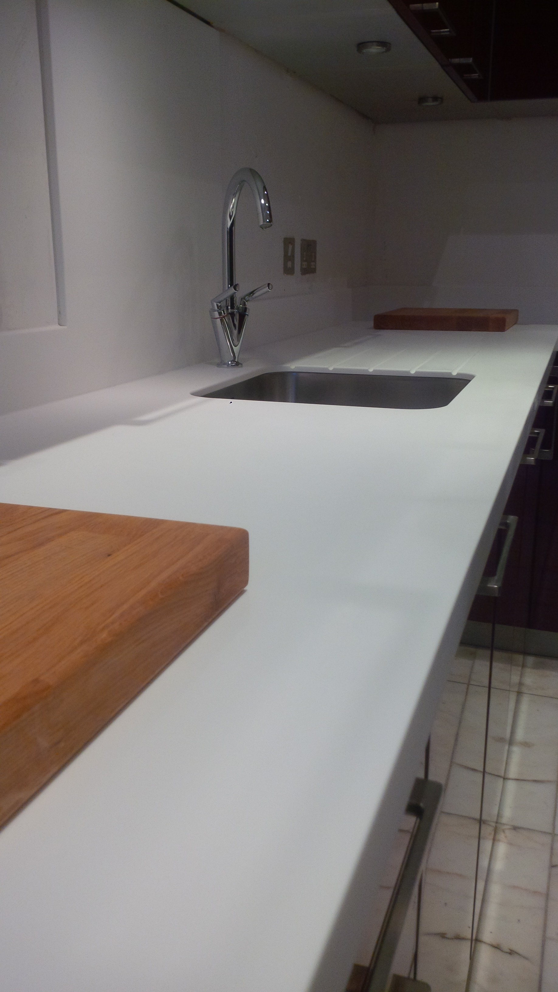 Replacement of granite worktops and upstands to glacier white corian and fitting of stainless steel  sink, by Designed Bespoke Joinery 1