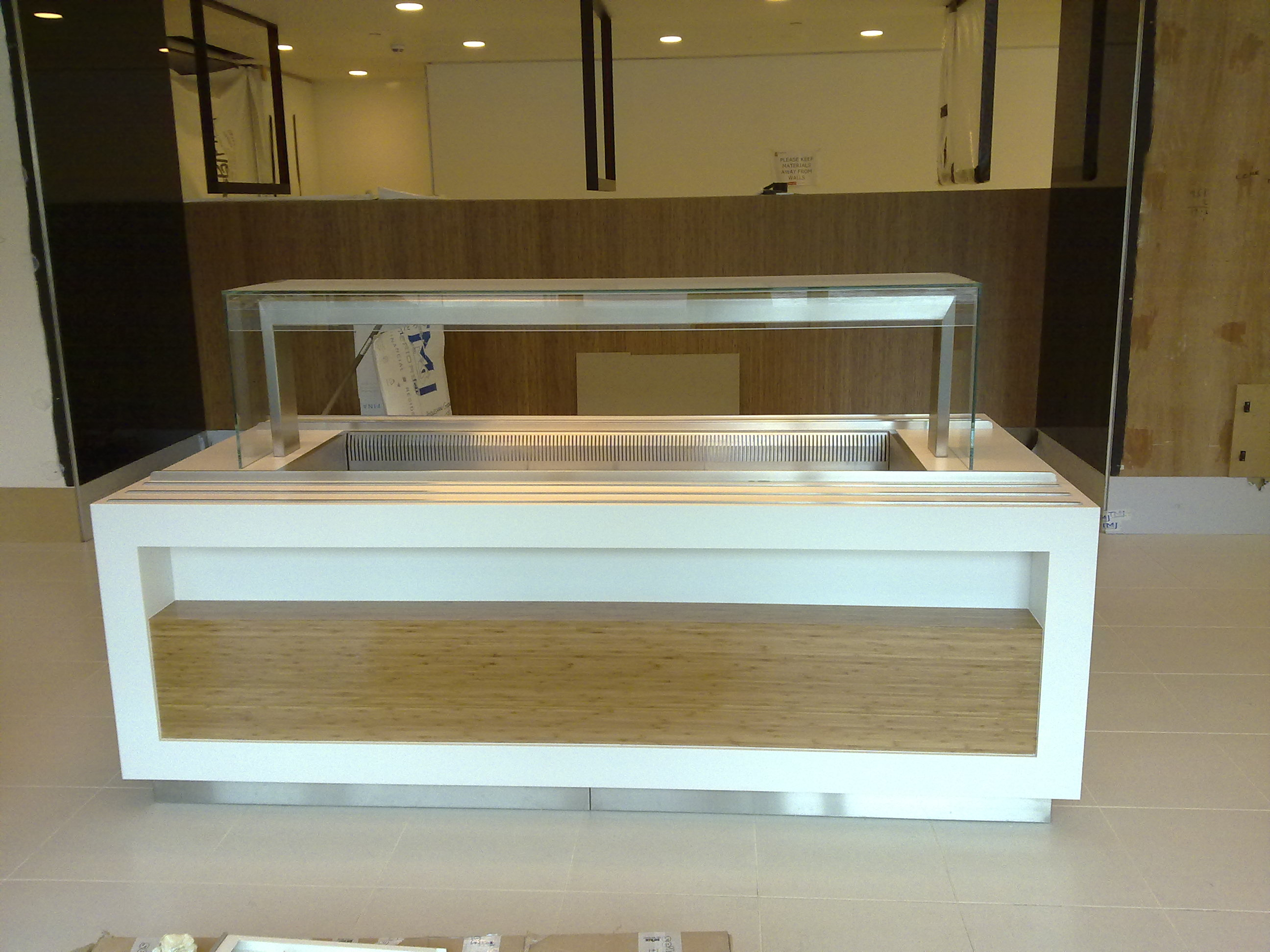 (Addleshaw) Law firm  – London  Glacier white corian and stainless steel tray runners throughout with bamboo veneer impulse displays